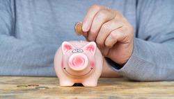 senior man hand putting money to piggy bank