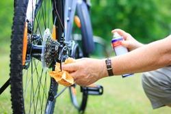 Senior man hands spraying an oil to chain from the wheel bike, doing maintenance