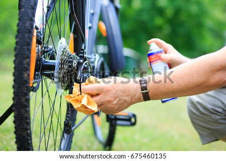 Senior man hands spraying an oil to chain from the wheel bike, doing maintenance #675460135