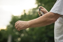 Senior man hands spraying mosquito / insect repellent in the forest