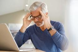 Senior man having migraine while working on laptop computer