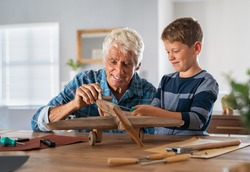 Senior man helping child to screw an airplane part that they are building together during summer vacation. Retired grandfather helping grandson in making wooden plane at home for school project.