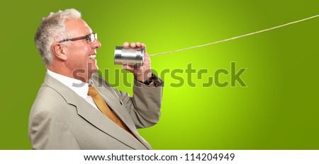 Senior Man Holding A Tin On Green Background