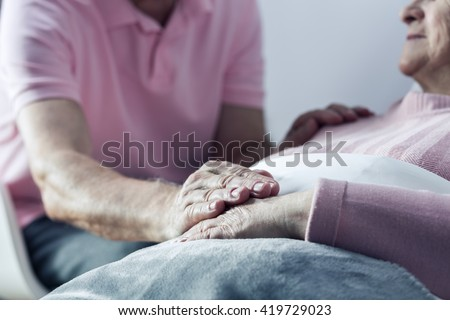 Senior man holding hand of his ill wife, close up