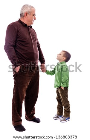 Senior man holding his grandson's hand, both with one hand in pocket, isolated on white background