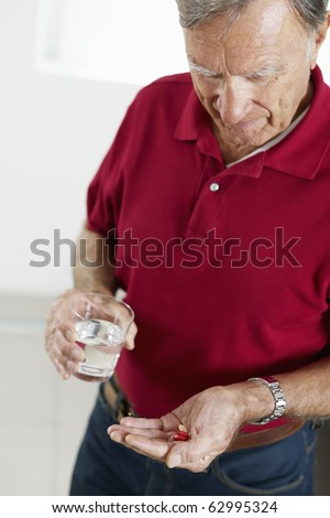 Senior man holding pills. Vertical shape, side view, waist up