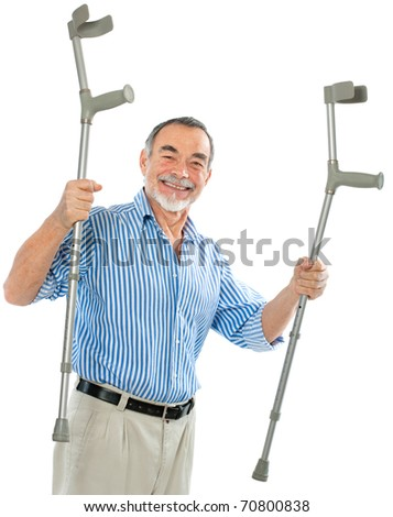 senior man holding the crutches smiling.