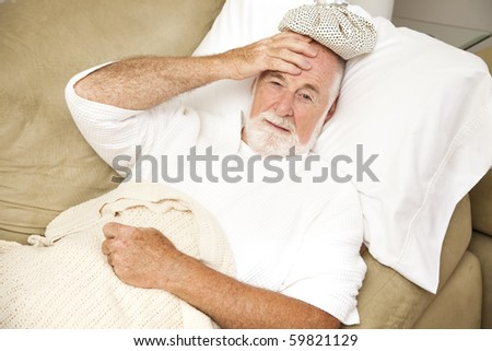 Senior man home sick in bed, with an ice pack on his head.  Could be hangover or illness.