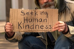 Senior man homeless beggar with a gray beard in a shabby clothes with a carboard sign sitting outdoors in city and asking for money donation. Sign on paperboard Seeking Human Kindness
