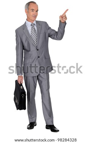 Senior man in a suit pointing skywards - stock photo
