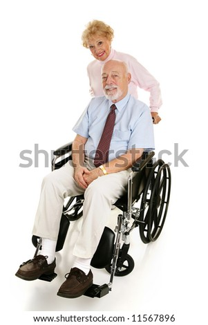 Senior man in a wheelchair with his loving wife pushing him.  Full body on white.