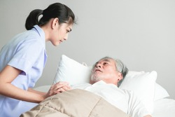Senior man in bed having bed dream with nurse come in and calm him down. Old asian man and beautiful asian nurse woman in bedroom. Senior home service concept.