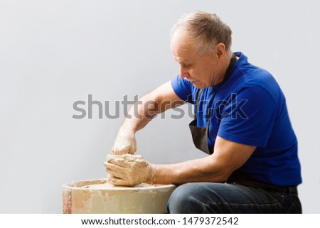 Senior man in casual clothes and aprons making ceramic pot on pottery wheel in workshop. hobby on pension