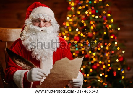 Senior man in costume of Santa Claus holding feather and Christmas letter
