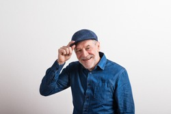 Senior man in denim shirt and flat cap smiling, studio shot.