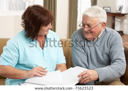 Senior Man In Discussion With Health Visitor At Home