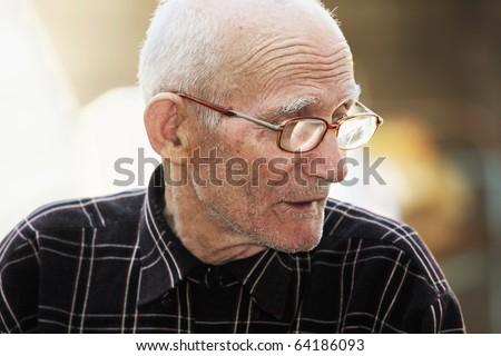 Senior man in eyeglasses looking sideways outdoor portrait