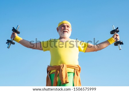 Senior man in gym working out with weights. Happy Senior man exercising with lifting dumbbell outdoor. Portrait of senior man holding dumbbell