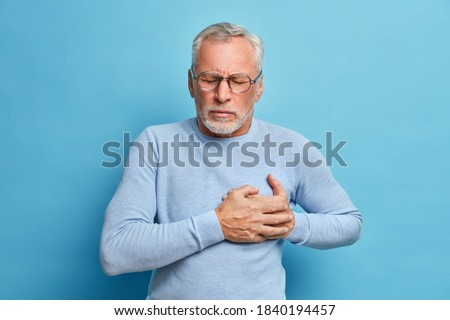 Senior man in spectacles presses hand to chest has heart attack suffers from unbearable pain closes eyes wears optical glasses poses against blue background. People age and problems with health Stockfoto ©