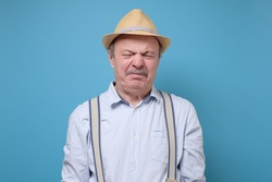 Senior man in summer hat with disgusted expression repulsing something. Disgust concept. Human emotions, facial expression concept. Studio shot blue wall.