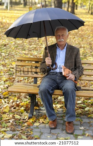 senior man in the park with umbrella