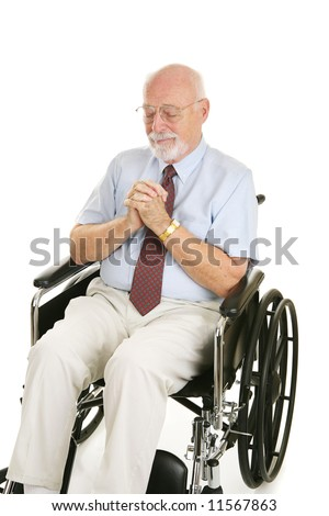 Senior man in wheelchair prays to recover his health.  Isolated on white.