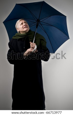 Senior man in winter clothes holding an umbrella
