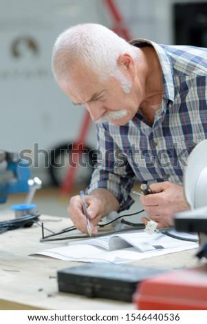 senior man in workshop senior man working in workshop