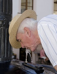 Senior man is drinking from the fountain to the city walk.