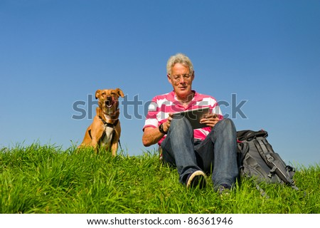 Senior man is reading information at the tablet PC outdoor