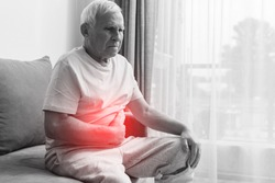 Senior man is suffering from problems with a digestion at home