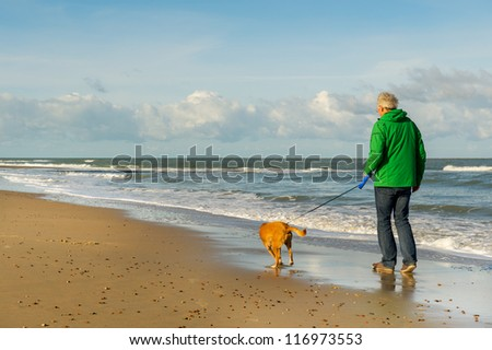 Senior man is walking the dog at the beach