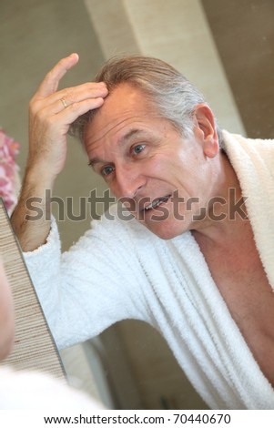 Senior man looking at hair in mirror