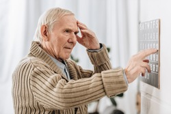 senior man looking at wall calendar and touching head