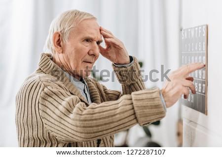 senior man looking at wall calendar and touching head Сток-фото ©