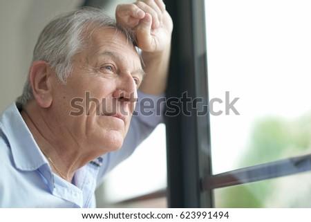 Senior man looking by window #623991494