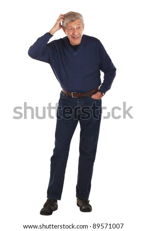 Senior man looks aside, scratching his head, with other hand in pocket. Standing full figure faces forward, wearing dark blue jeans and v-necked long sleeved shirt. Vertical format isolated on white.