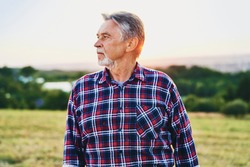 Senior man looks over his land at sunset