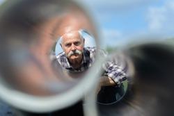 senior man looks through a metal tubes