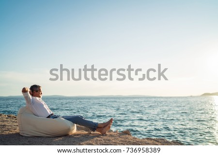 Senior man lying on deck chair on the beach during sunset #736958389