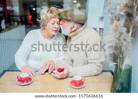 Senior man making marriage proposal to lady,dating sites for elder people.Propose happiness couple elderly caucasian relax weekend lifestyle in coffee shop. View from above.Sun glare Retirement Plan.
