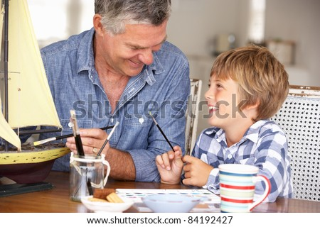 Senior man model making with grandson - stock photo