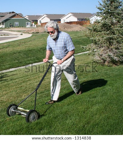 Senior man mowing grass with reel type mower.