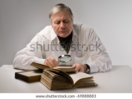 Senior man observing a book with a magnifying glass