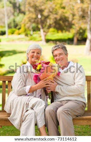 Senior man offering flowers to his wife - stock photo