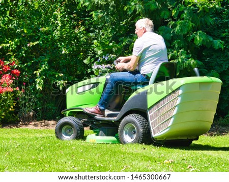 Senior man 75 old years driving a tractor lawn mower in garden with flowers. Green and white ride on mower, turning in field between colorful flowers #1465300667