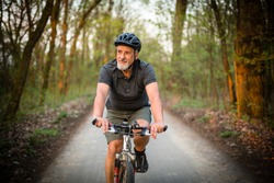 Senior man on his mountain bike outdoors (shallow DOF; color toned image)