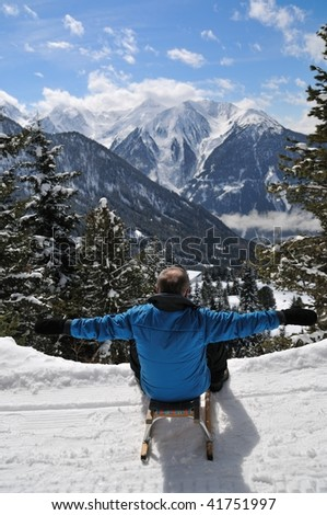 Senior man on sledge having fun in mountain snowy country