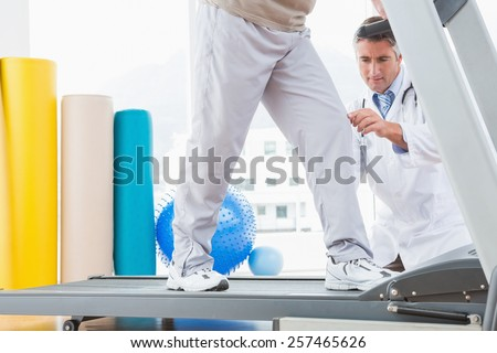 Senior man on treadmill with therapist crouching in fitness studio Stock photo ©