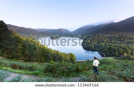 Senior man overlooks Grasmere in Lake District as sunrise as sun light mountains